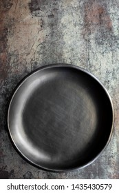 Empty rustic black plate on slate background, top view.