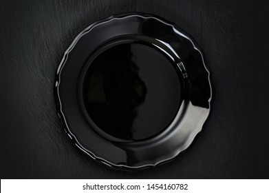 Empty rustic black plate on dark stone background, copy space, top view