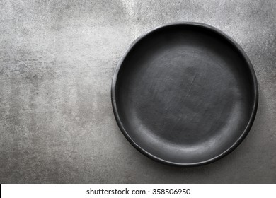Empty rustic black plate over gray slate.  Aerial view, with copy space.