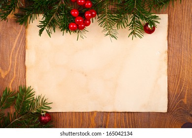 Empty rustic paper with juniper leaves and Christmas globes around, wooden background