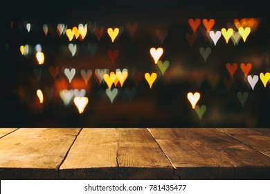 Empty rustic table in front of Valentine's day romantic glitter bokeh background with many hearts lights. Ready for product display montage