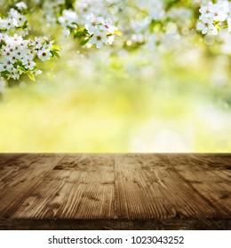 Empty rustic wooden table with cherry blossoms and spring background for a easter decoration