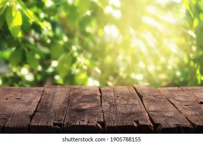 Empty rustic wooden table with defocused lush foliage at background. Backdrop for product display on top of the table.