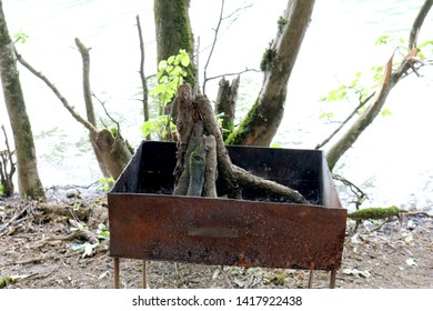 Empty rusty barbecue grill on the background of the lake. Old brazier or mangal with wood. Picnic concept
