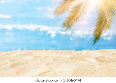Empty sand beach in front of summer sea and palm tree background with copy space