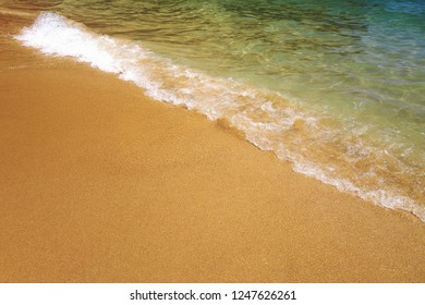 Empty sandy beach at Algarve coast, Portugal. White waves, crystal clear water