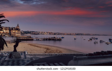 Empty sandy Praia do Ribeiro and fishing boats an bay with magenta sunset in Cascais, Portugal
