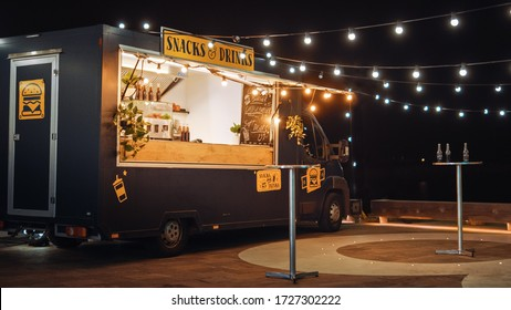 Empty Scene with a Dark Street Food Van Standing in the Evening in a Nice Warmly Lit Neighbourhood Next to the Sea. Food Truck Has Burgers and Drinks for Sale. Tables Have Bottles on Them.