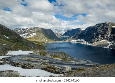 Empty scenic serpentine road at Dalsnibba plateau. Mountain lake and rocks in snow background. Geiranger, Norway.