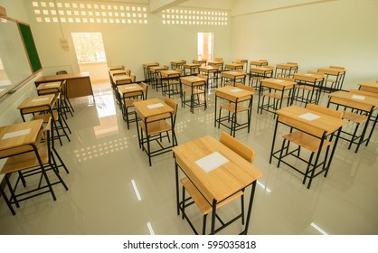Empty of  School classroom with test exam paper on desks chair wood, and blackboard at high school Thailand, education concept