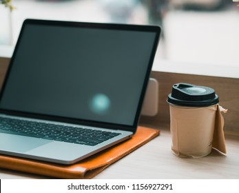 Empty screen laptop with hot cup of coffee on the bar of the cafe.