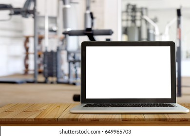 Empty screen laptop  on top wooden table space platform and fitness gym background. For graphic or product display montage.
