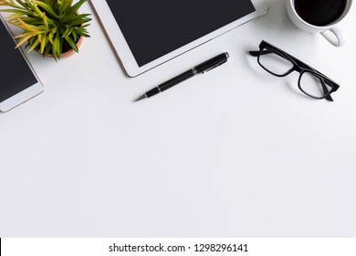 Empty screen Smart phone and tablet with cup of coffee on business desk office with copy space, Top view