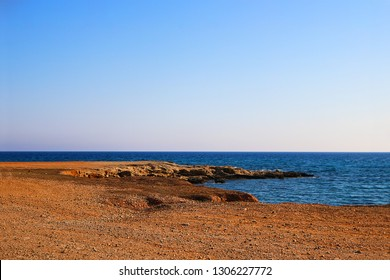 empty sea shore, Landscape with red shore, rocks, sea and blue sky. Travel. Unpopular place not for tourists. Cyprus