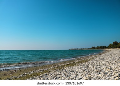 empty sea shore with white pebble, Landscape sand and round sones on the shore, trees far away, sea and blue sky. Travel. Unpopular place not for tourists. Cyprus, Mediterranian, Larnaca, Pervolia