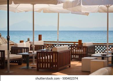 Empty seaside terrace restaurant on sunny day.