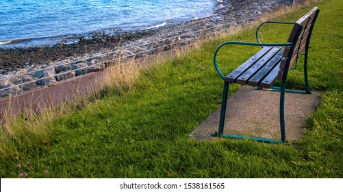 An empty seat/bench on a grassy area looking down towards the sea.