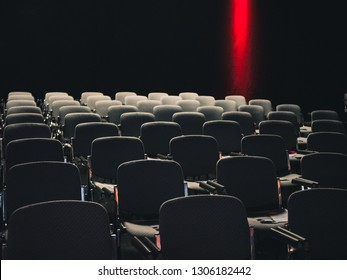 Empty seats in a dark room at a business conference, red light in background