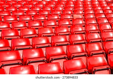 Empty seats red at outdoor stadium.