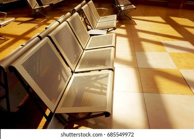 Empty seats in terminal hall at the airport with golden sunshine.