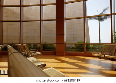 Empty seats in terminal hall at the airport with golden sunshine with outside view.
