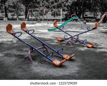 Empty seesaw, chain swing and playground slide in old playground in public park. Childhood memories concept.