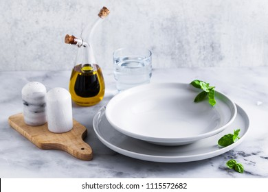 Empty set of plates for soup on a table with spices and olive oil in a decanter.