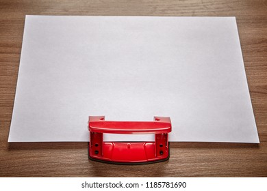 An empty sheet of white paper is inserted into slit of red steel office hole puncher, mockup with a copy-space.