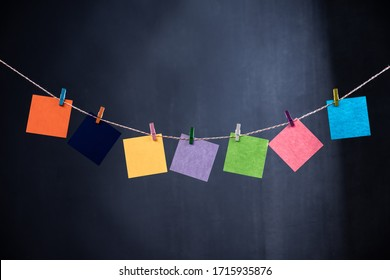 Empty sheets of paper for notes that hang on a rope with clothespins and isolated on a black background. Blank cards on a mockup template.