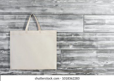 Empty shopping bag hanging on wooden wall. Ad and buy concept. Mock up