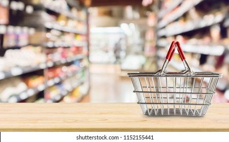 Empty Shopping basket on wood table over grocery store supermarket blur background