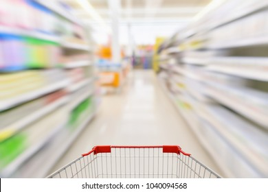 Empty shopping cart with abstract blur supermarket discount store aisle and product shelves interior defocused background