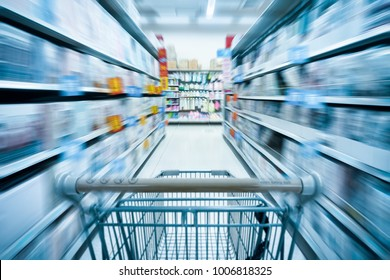 empty shopping cart and abstract blurred supermarket background
