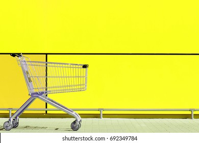 Empty Shopping Cart for buyer, parked in front of large supermarket. Consumerism concept