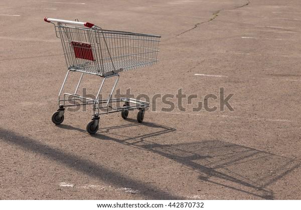 Empty shopping cart on asphalt