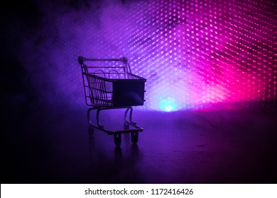 Empty shopping trolley on dark toned foggy background with some copy space. Financial crisis concept.