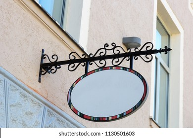 empty signboard hanging from metal frame at house wall