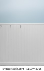 Empty silver hooks on white bead board or wainscoting with light blue wall paint