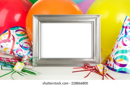 Empty Silver Photo Frame with Birthday Party Decorations including balloons,party hats and noisemakers