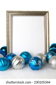 Empty Silver Photo Frame with Blue and Silver Christmas Ornaments on a White Background