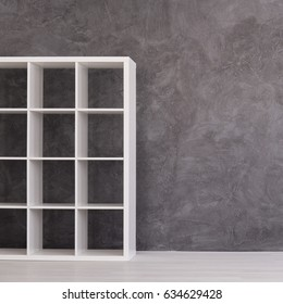 Empty simple shelving unit in modern interior with cement wall