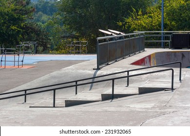 Empty skatepark at noon with ramps, grind rails, half pipe and fitness equipment.