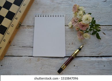 Empty sketchbook on wooden desk with roses, chessboard and fountain pen. Mockup for elegant design.