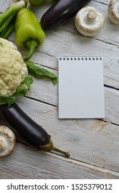 Empty sketchbook on wooden desk with different vegetables and greens - view from the top, flat lay. Organic products and healthy lifestyle  photography. Mockup for elegant design.
