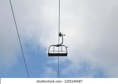 Empty ski lift chair against cloudy sky