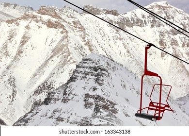 An empty ski lift chair bringing color amid the otherwise colorless world of a mountain ski hill.