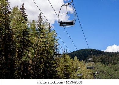 Empty ski lift seats in alpine summer landscape