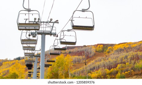empty ski lift surrounded by mountain slopes covered in brilliant autumn colors