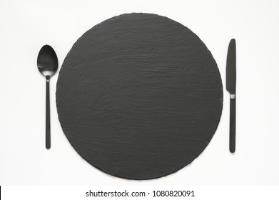 Empty slate plate and black silverware on white background. Top view point.
