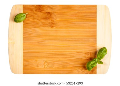 Empty smooth cutting board. Wooden kitchen board and basil leafs.